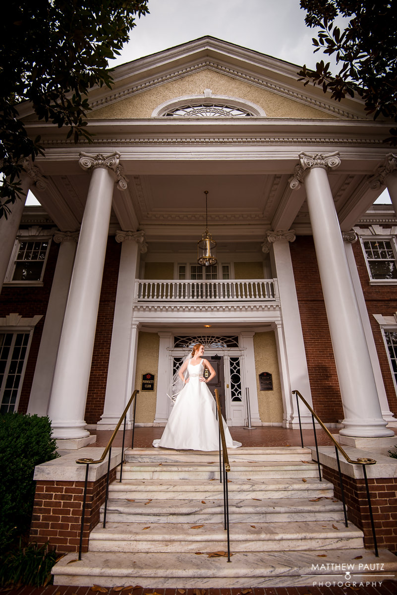 Bride in dress posing out in front of the Poinsett Club