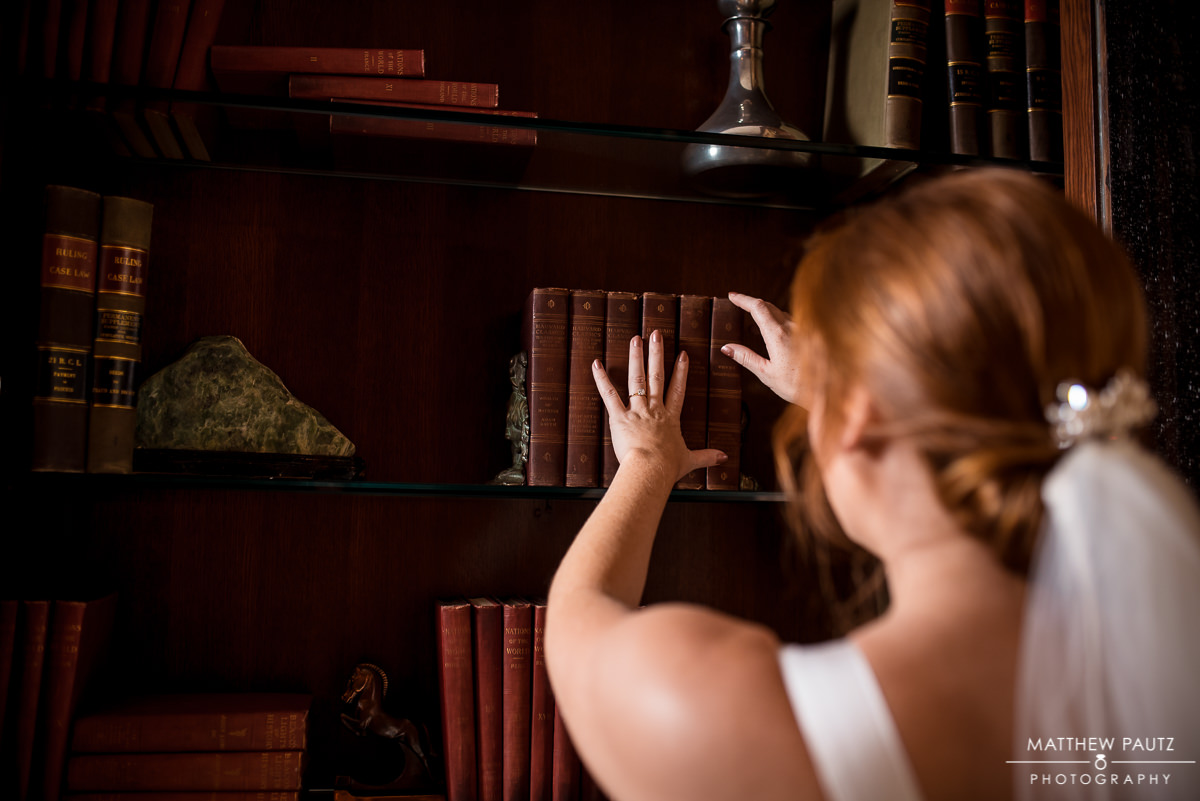 Bride touching books in library