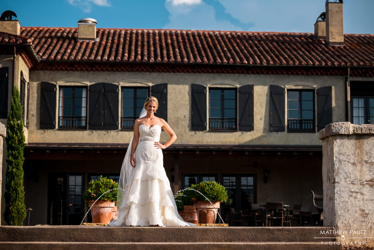 bride posing out in front of a chateau style hotel