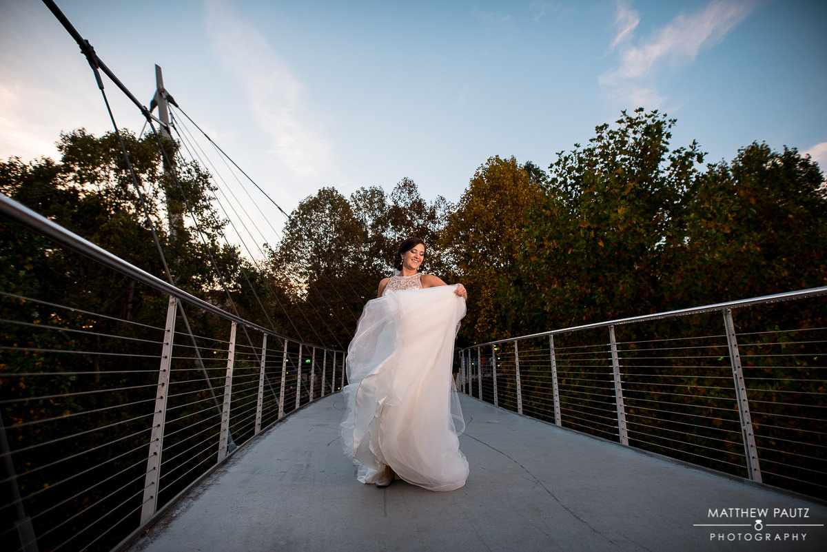 Bride twirling her dress on a bridge in Greenville