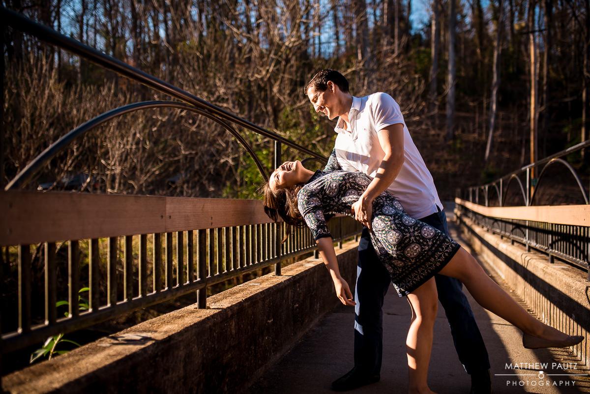 Engaged couple having fun dancing on a bridge
