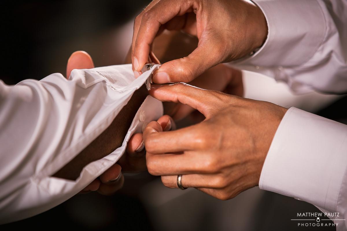Closeup of groomsmen putting on cufflinks