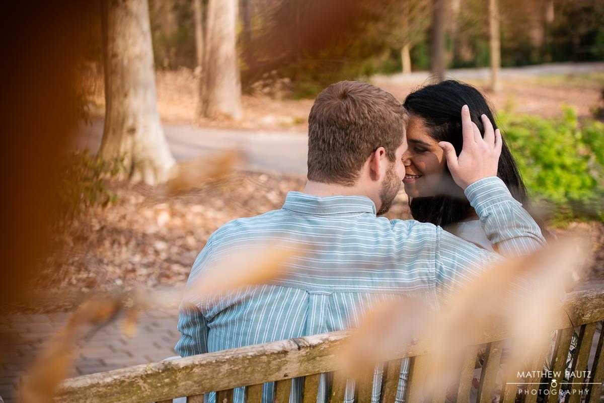 couple sitting on bench in botanical garden