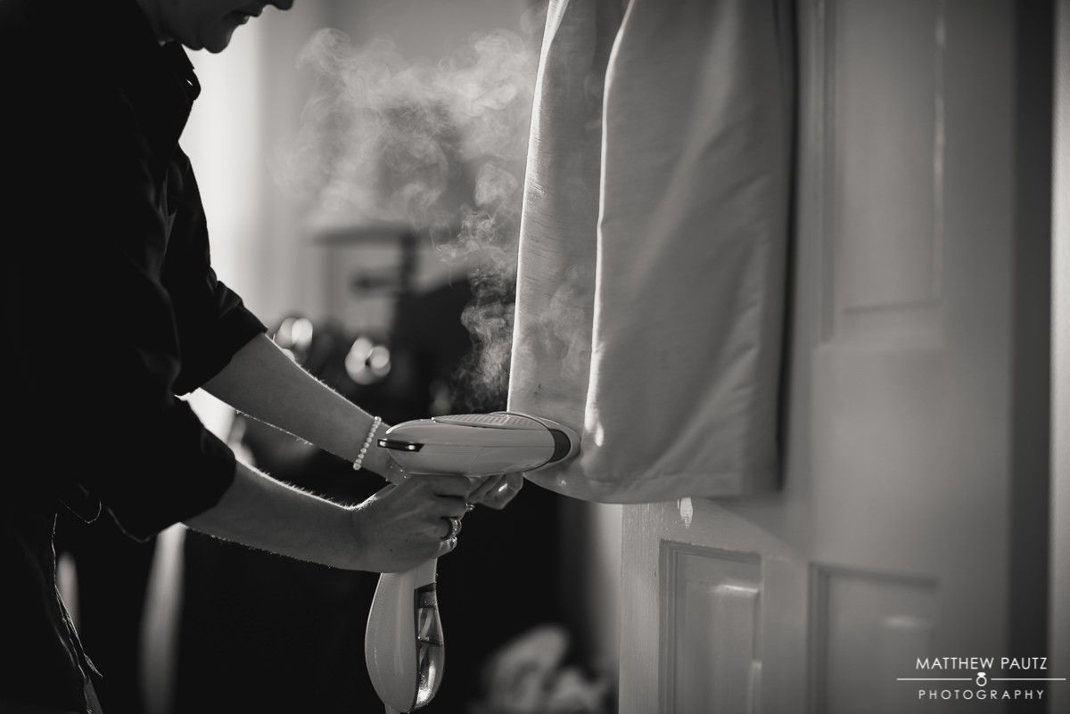 bridesmaids steam cleaning dress before wedding