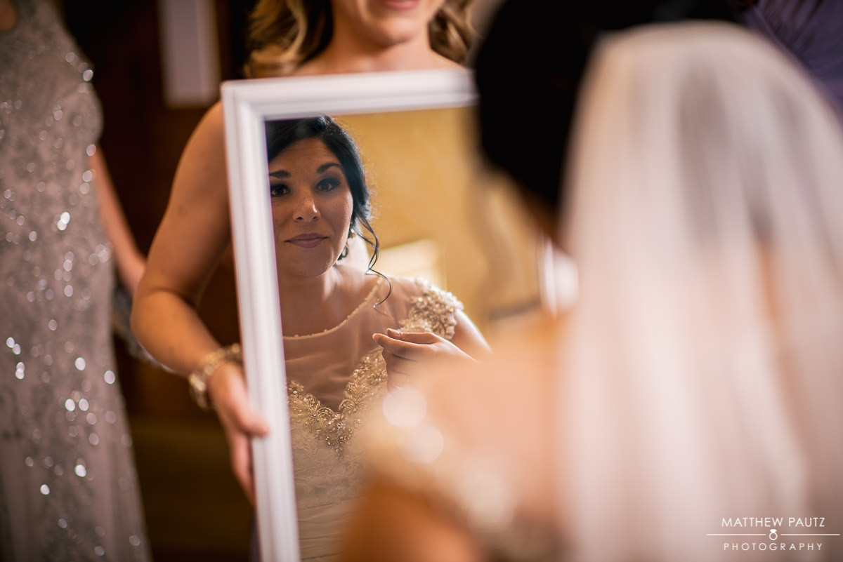 bride looking at reflection of herself in mirror